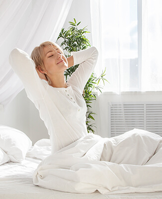 Woman Waking Up and Stretching Out of Bed Sheets
